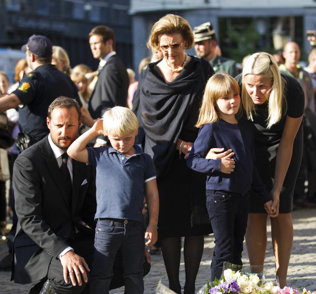 MIDT BLANT FOLKET: Da terroren rammet Norge i 2011 var det svært viktig for kronprinsfamilien og den øvrige kongefamilien å vise folket at de sto sammen i sorgen. Her forklarer Haakon og Mette--Marit prins Sverre Magnus og prinsesse Ingrid Alexandra hvorfor folk har lagt ned blomster foran Oslo Domkirke. Farmor dronning Sonja i bakgrunnen. Foto: NTB Scanpix