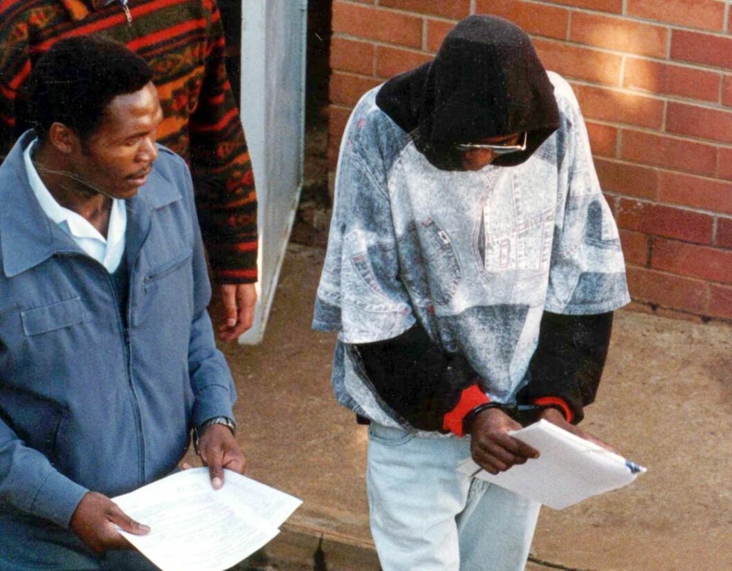 <strong>MOSES SITHOLE:</strong> Sithole (til høyre) blir ledet vekk fra retten året før han ble dømt til mer enn 2400 år i fengsel fredag 5.desember 1997.  Foto: AP