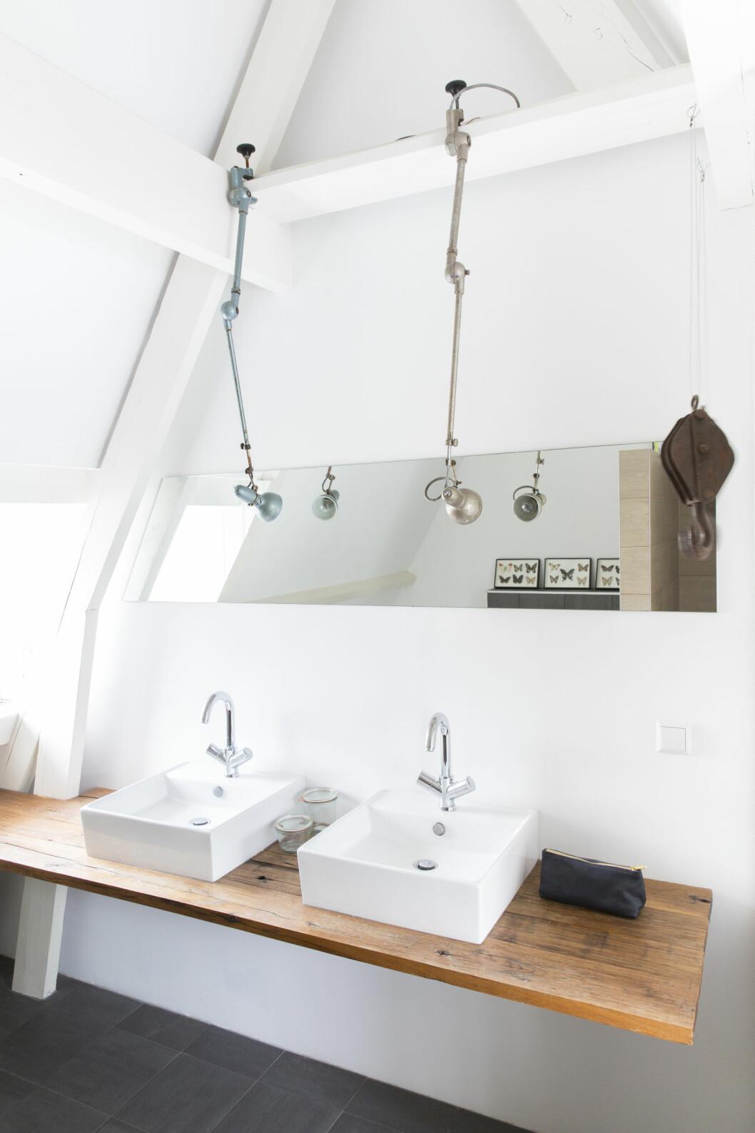 GJENBRUK: Baderomsbenken er laget av materiale fra gamle togvogner mens servanten er fra Kvik. Lampene og de originale håndklekrokene som henger fra taket, er fra Brût Amsterdam.   Foto: Margriet Hoekstral