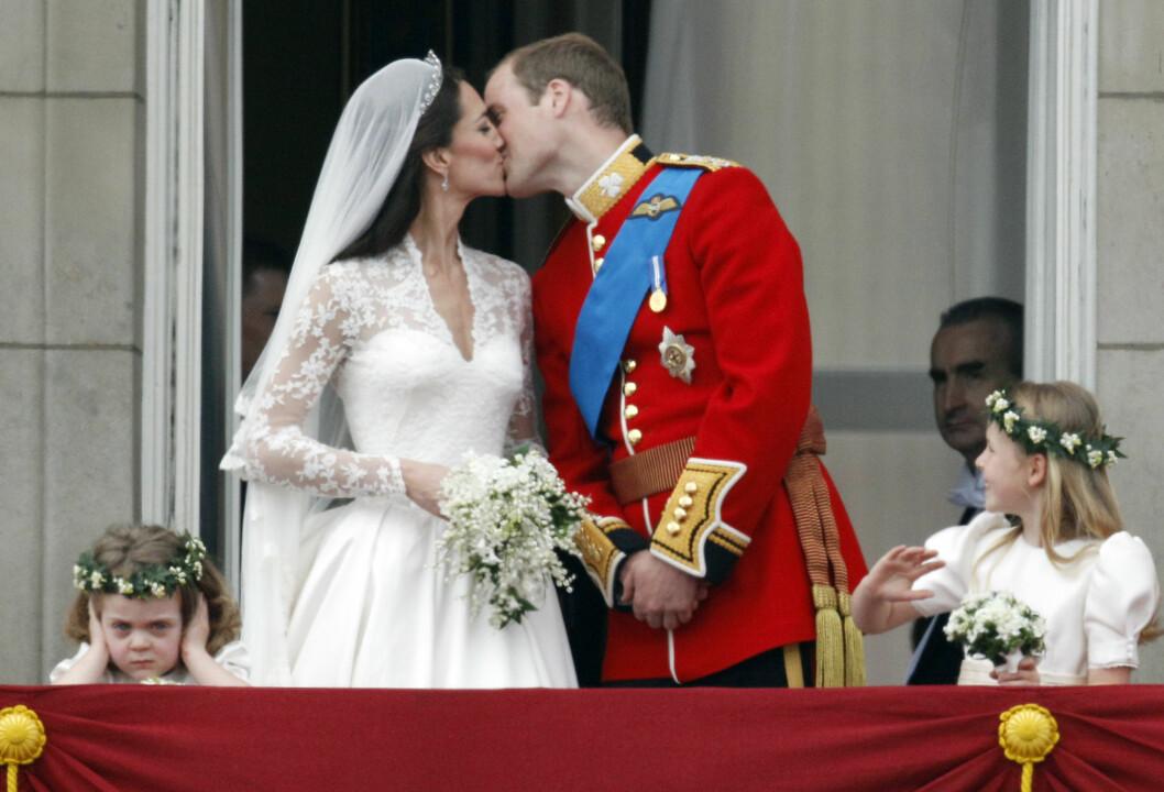 KYSSET: Det vakte ellevill jubel da William og Kate kysset hverandre på balkongen på Buckingham Palace. Det er mulig brudepike Grace van Cutsem (t.v.) syntes det ble for for mye stå-hei fra folkemengden - hun måtte nemlig holde seg for ørene. Brudepike Margarita Armstrong-Jones til høyre. Foto: NTB Scanpix