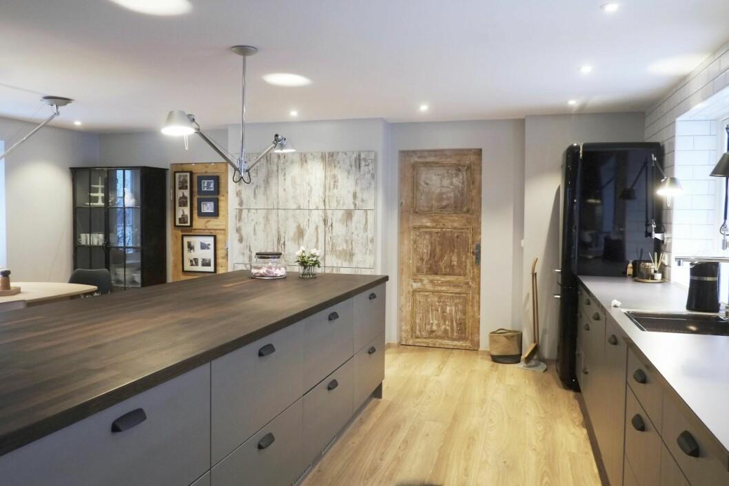 FINE FLATER: Kjøkkeninnredningen fra trønderske Fossline er malt i en grå tone og har kjøleskuffer. Lampene er italiensk design. Foto: Hege Landrø Johnsen