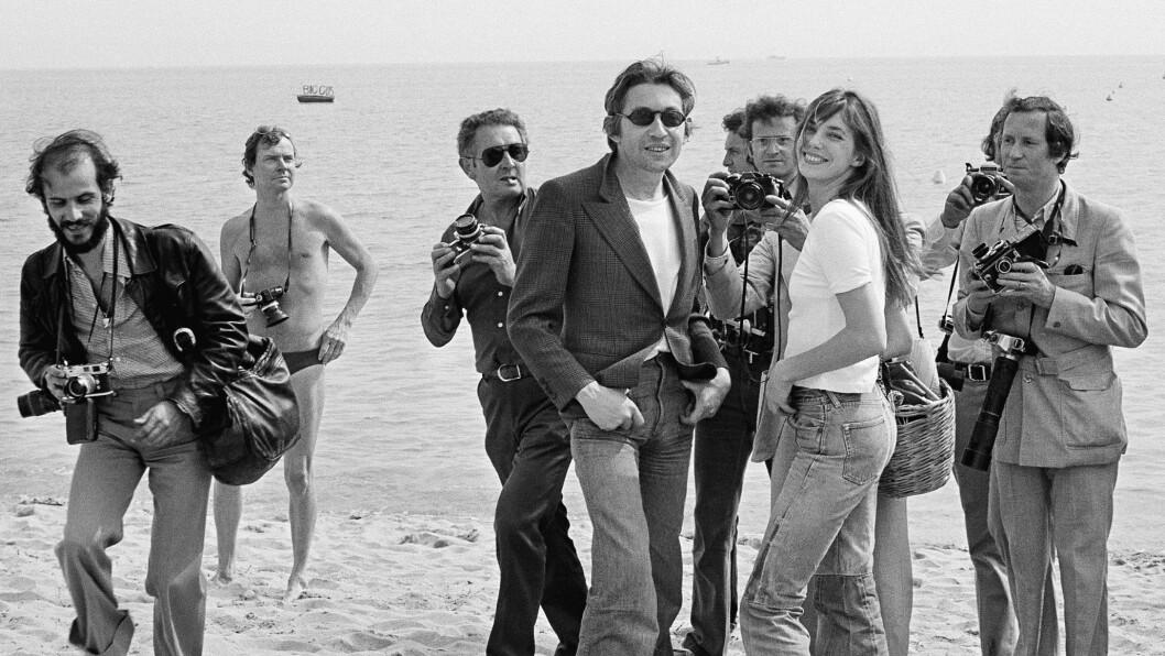 <strong>BIRKIN:</strong> Serge Gainsbourg og Jane Birkin omringes av fotografer under filmfestivalen i Cannes i 1974. Sju år etter at dette bildet ble tatt skulle vesken Birkin har rundt skulderen bli byttet ut med noe langt mer eksklusivt. Les hele historien bak den verdensberømte Birkin-vesken lengre ned i saken. Foto: Ap