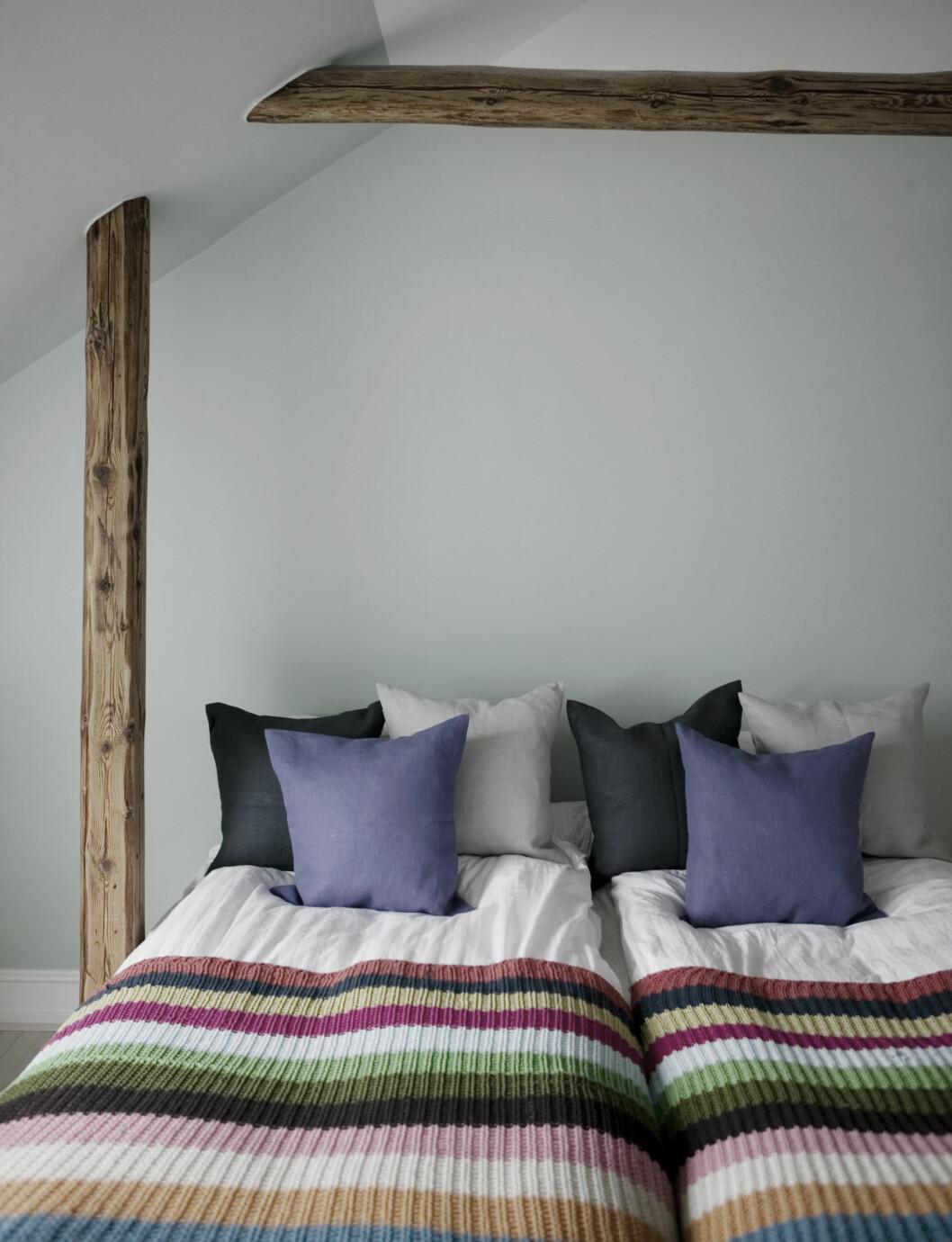 KOSELIG SOVEROM: Dobbeltsengen får bare så vidt plass mellom bjelkene på soverommet. Pledd fra Ikea.  Foto: Kira Brandt/House of Pictures