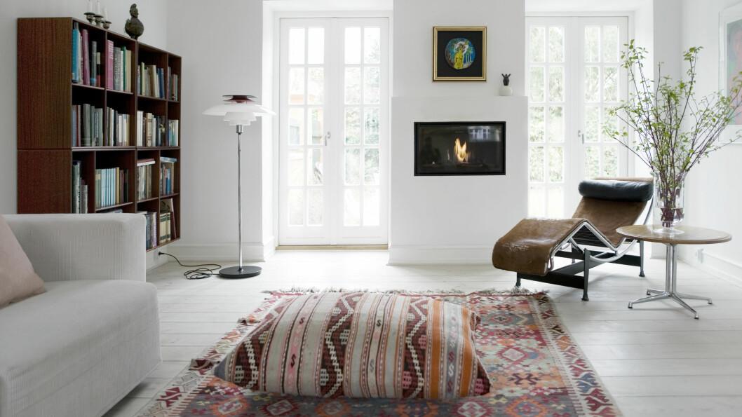 PENT MED ARVEGODS: Kelimteppet og den store puten på gulvet er arvegods, det samme er Le Corbusier-stolen med kuskinn. Gasspeisen er fra livingflame.dk. Foto: Kira Brandt/House of Pictures