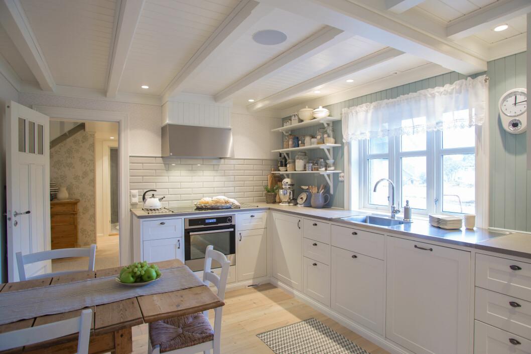 KOSELIG: I kjøkkenet er gulvet senket, og det er nytt tak. Skapene er fra Ikea, men innramming og sokkel er hjemmesnekret. Døren er en favoritt, og oppkalt etter svigerfar – «Inge-døren». Foto: Siv-Elin Nærø