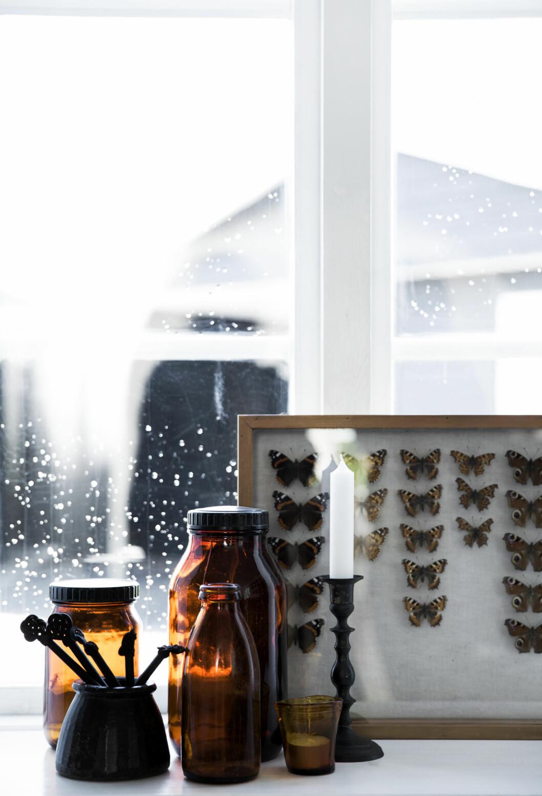 GYLNE TONER: En samling med gamle melkeflasker ikonjakkfarget glass plukker opp de gylne tonene som dominerer i hele huset.  Foto: Tia Borgsmidt