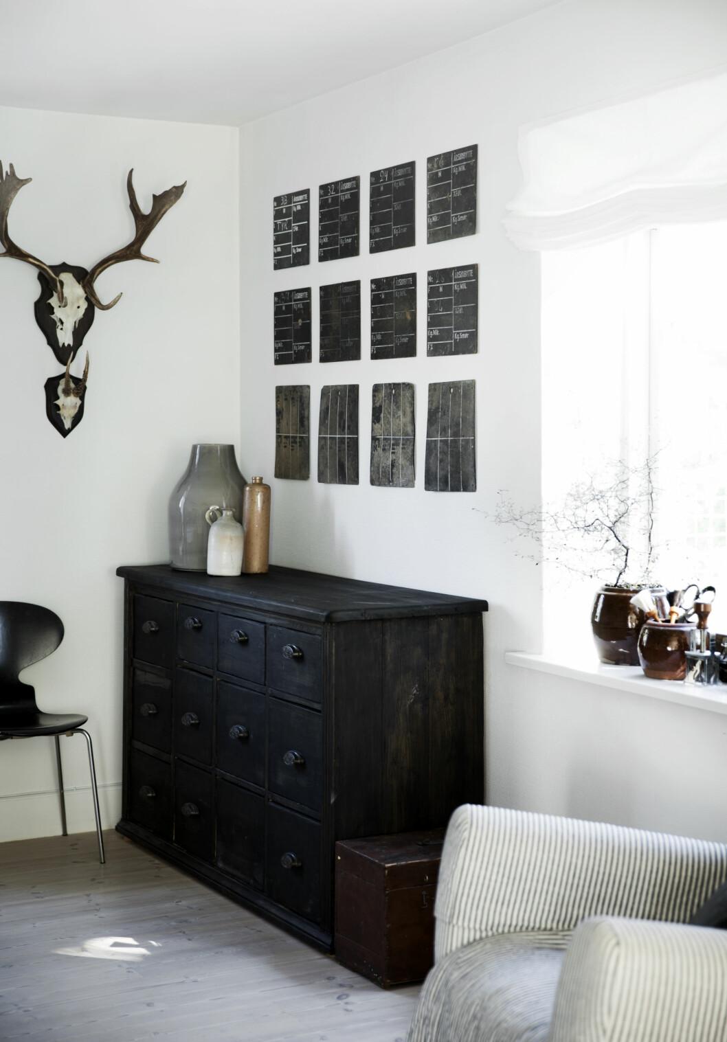 GJENBRUK: Over kjøpmannsdisken har Birgitte hengt 12 små, gamle tavler som sammen danner en stilren symmetri. Egentlig så hun for seg énstor tavle, men siden hun elsker gjenbruk, ble dette et artig alternativ.  Foto: Tia Borgsmidt