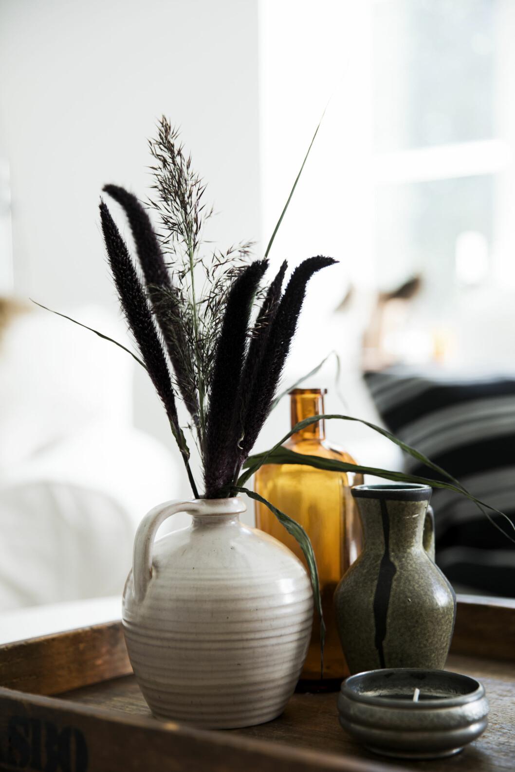 PYNT PÅ STUEBORDET: Den lille samlingen med farget glass og keramikk på stuebordet plukker opp nyansene i rommet.  Foto: Tia Borgsmidt