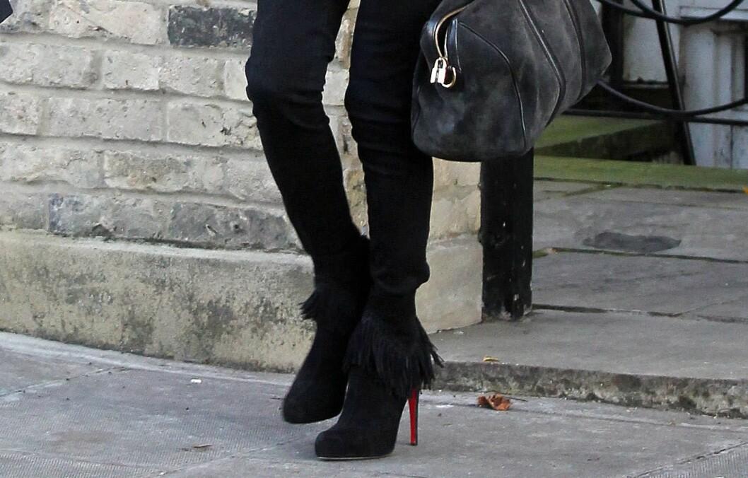 MED BUKSEN OPPI ANKELSTØVLENE: Supermodell Kate Moss går for smale svarte skinnyjeans som hun stapper litt løst oppi sine skyhøye semskede ankelboots fra Christian Loubotuin.  Foto: All Over Press