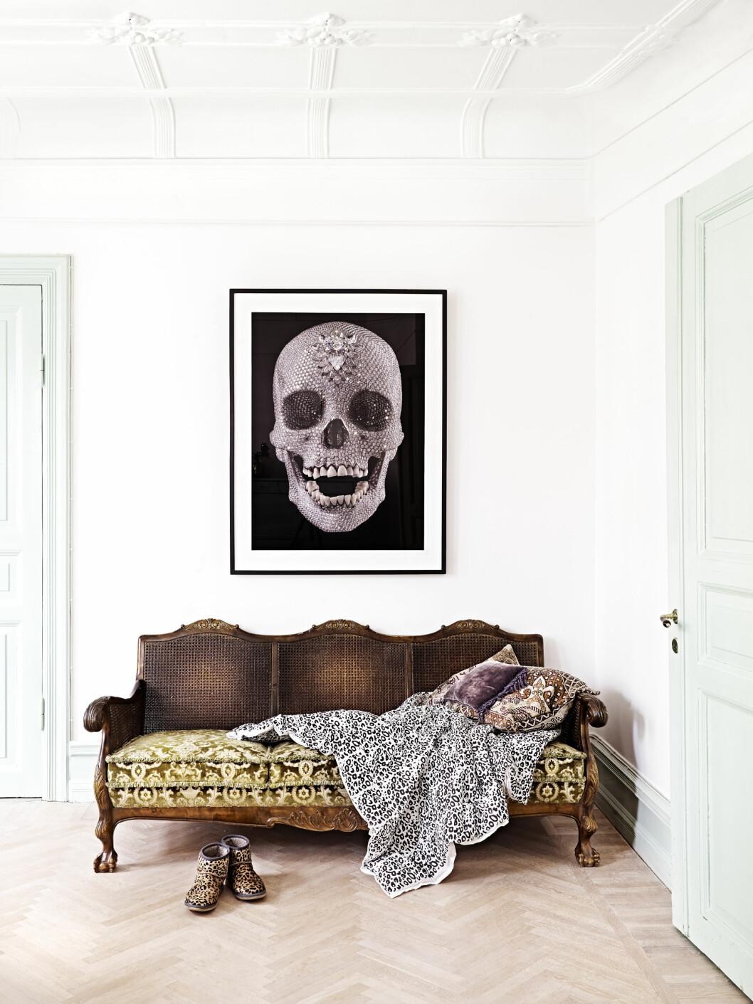 KONTRAST: Et stort rocka bilde på veggen og en bestemorssofa blir en perfekt miks sammen.  Foto: Sara Svenningrud