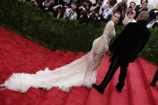 KIM KARDASHIAN I NORSK DESIGN: En av verdens største kjendiser, Kim Kardashian, møtte opp i en kjole designet av norske Peter Dundas for Roberto Cavalli. Her er hun i kreasjonen på den røde løperen sammen med ektemannen Kanye West. Foto: Afp