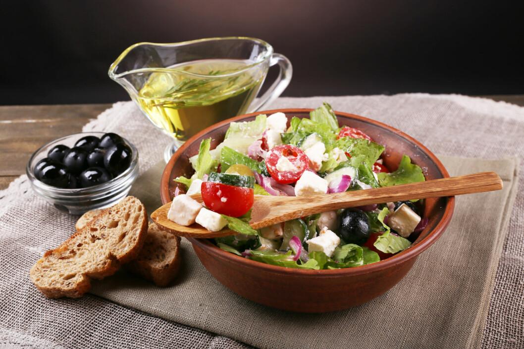 Bowl of Greek salad served with olive oil on sacking napkin on wooden table on dark background Foto: Africa Studio - Fotolia