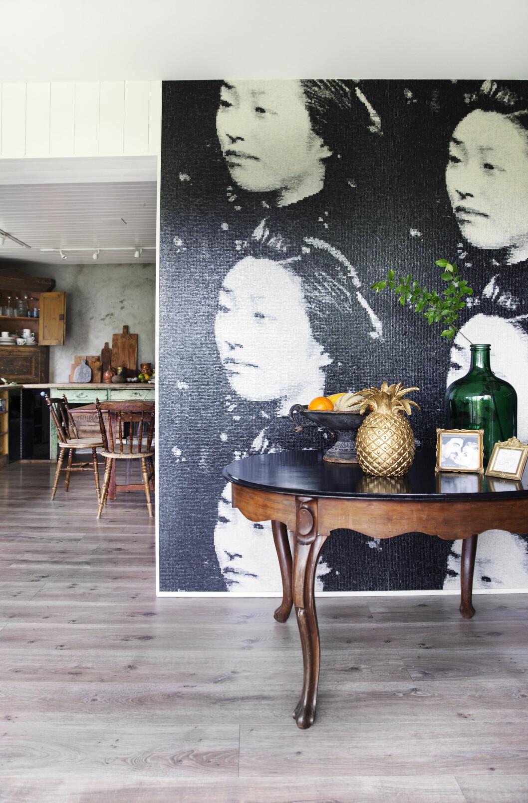 Det gamle bordet blir spesielt vakkert mot det glassaktige, moderne tapetet fra franske Élitis. Foto: Yvonne Wilhelmsen