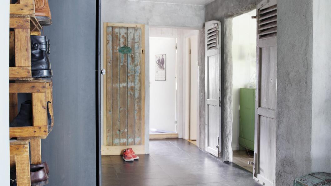Med fire barn inn og ut, er steinflisene et praktisk valg i gangen. En stabel med gamle kasser fungerer som skohylle. TIPS: Polert stein, røft treverk og matte vegger. Ulike teksturer framhever det vakre i hverandre!  Foto: Yvonne Wilhelmsen
