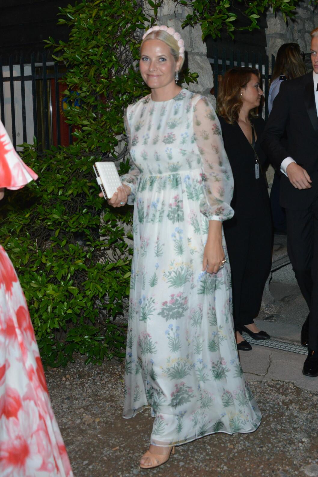 BLOMSTERPIKE: Mette-Marit var kledd i en blomstermønstret kjole er fra Valentinos pre fall-kolleksjon for 2015 og nagleveske fra samme merke. Det hele var toppet med en unik hårpynt av kråkeboller. Foto: Splash News/NTBscanpix
