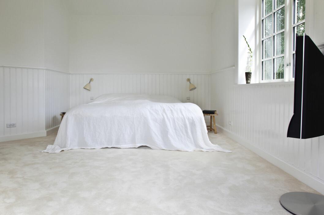 MINIMALISTISK: Et soverom helt uten forstyrrende elementer. En stor seng, enkle nattbord og hvite vegger, gulv og tak skaper den totale roen.  Foto: Iben & Niels Ahlberg