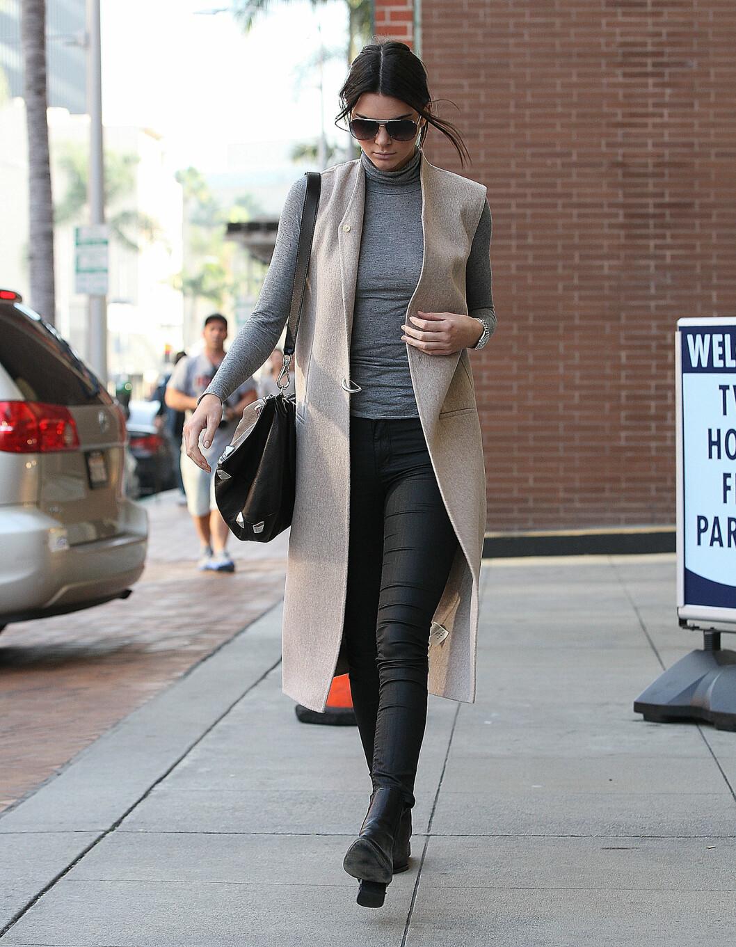 Supermodell Kendall Jenner gikk for et langt mer stilrent antrekk, og la til en enkel, lang vest over den høyhalsede genseren.  Foto: Scanpix