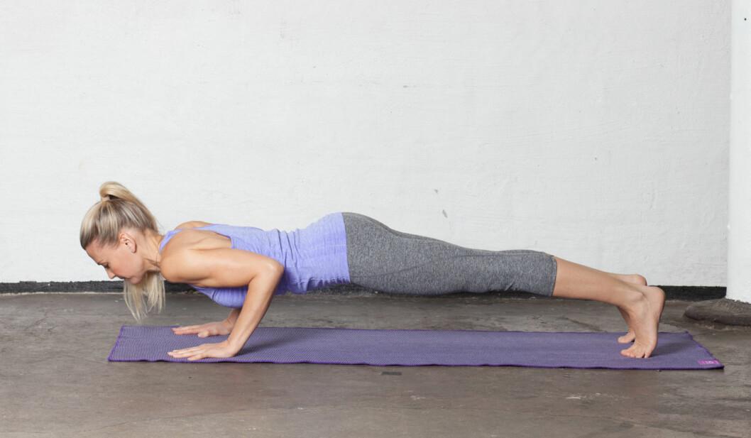 5: Pust ut og ta et steg tilbake med ett ben om gangen til du står i planken. Skuldrene skal være rett over håndleddene. Aktiver de indre magemusklene ved å trekke navlen inn, og trekk skuldrene tilbake mot ryggen. Bøy så albuene til chaturanga dandasana. Skuldrene skal være på linje med albuene, albuene på linje med håndleddene. Forestill deg at du trekker ribbena inn mot kroppens midtpunkt, og forleng halevirvelen mot hælene.  Foto: Ida Bjørvik