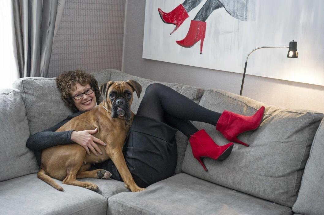 FORFENGELIG: Anne Grethe liker å pynte seg med høye hæler. Vel å merke når hun sitter. Bildet på veggen, som nevøen hennes har malt, illustrerer Anne Grethe med sine røde pumps. Hunden Elsa Sophie (14 mnd) deler hun med sønnen.