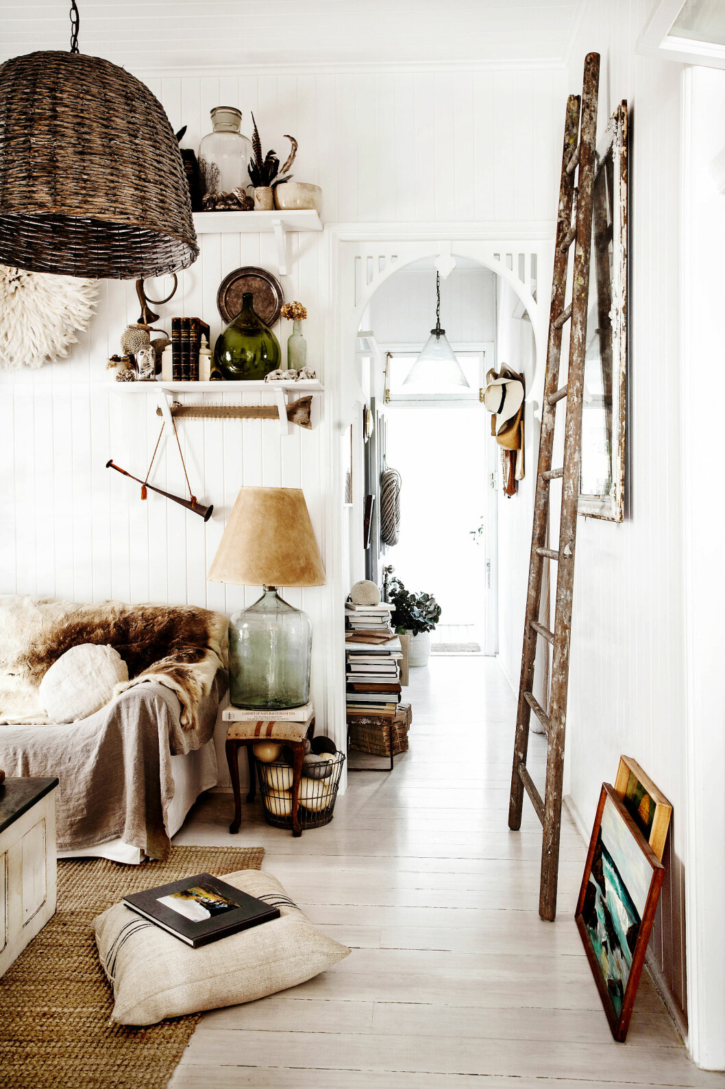 HJEMMELAGET: Stuen er rommet for en rolig stund i sofaen med det lunende reinsdyrskinnet. Lampen har Kara laget av en gammel glassflaske, - en demijohn, som tidligere ble brukt til oppbevaring, transport og salg av blant annet oljer, eddik, vin og øl.En gammel stige brukt til epleplukking dekorerer veggen. Foto: Kara Rosenlund