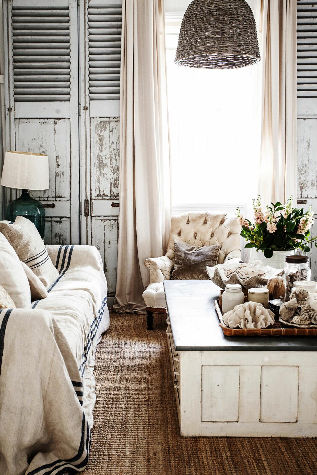 STUA: Vinduene i stuen kan lukkes med gamle vindusskodder. Sammen med en gammel, søt lenestol og et gammelt arkivskap som fungerer som sofabord, gjør de stuen helt særegen. Dekorasjonen består av skjell og koraller.  Foto: Kara Rosenlund