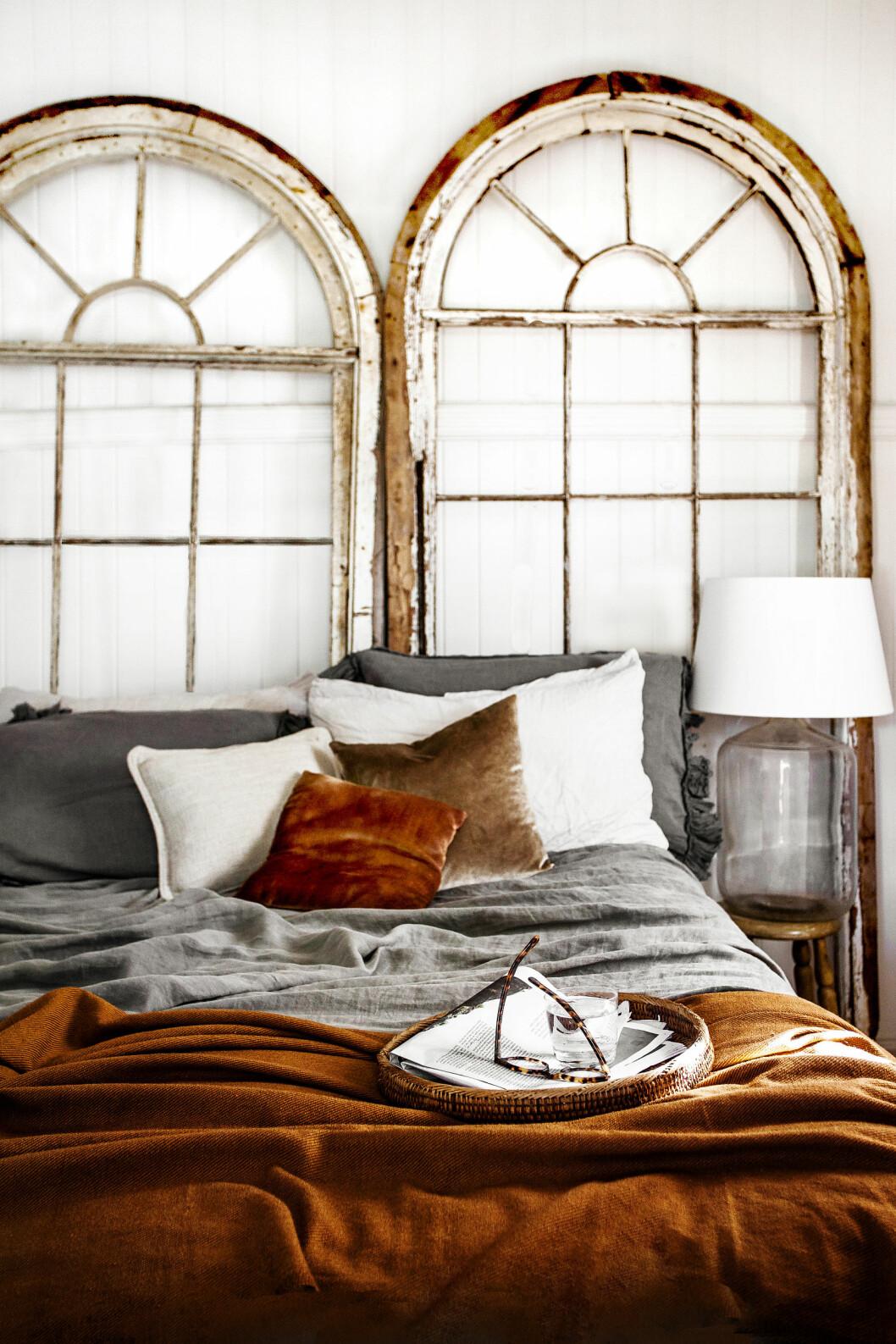 SOVEROMMET: De gamle, vakre buedørene flyttet Kara rundt hele huset, før de endelig fant sin plass som hodegjerde på sengen. Sengetøyet og sengeteppet er vintage. Foto: Kara Rosenlund