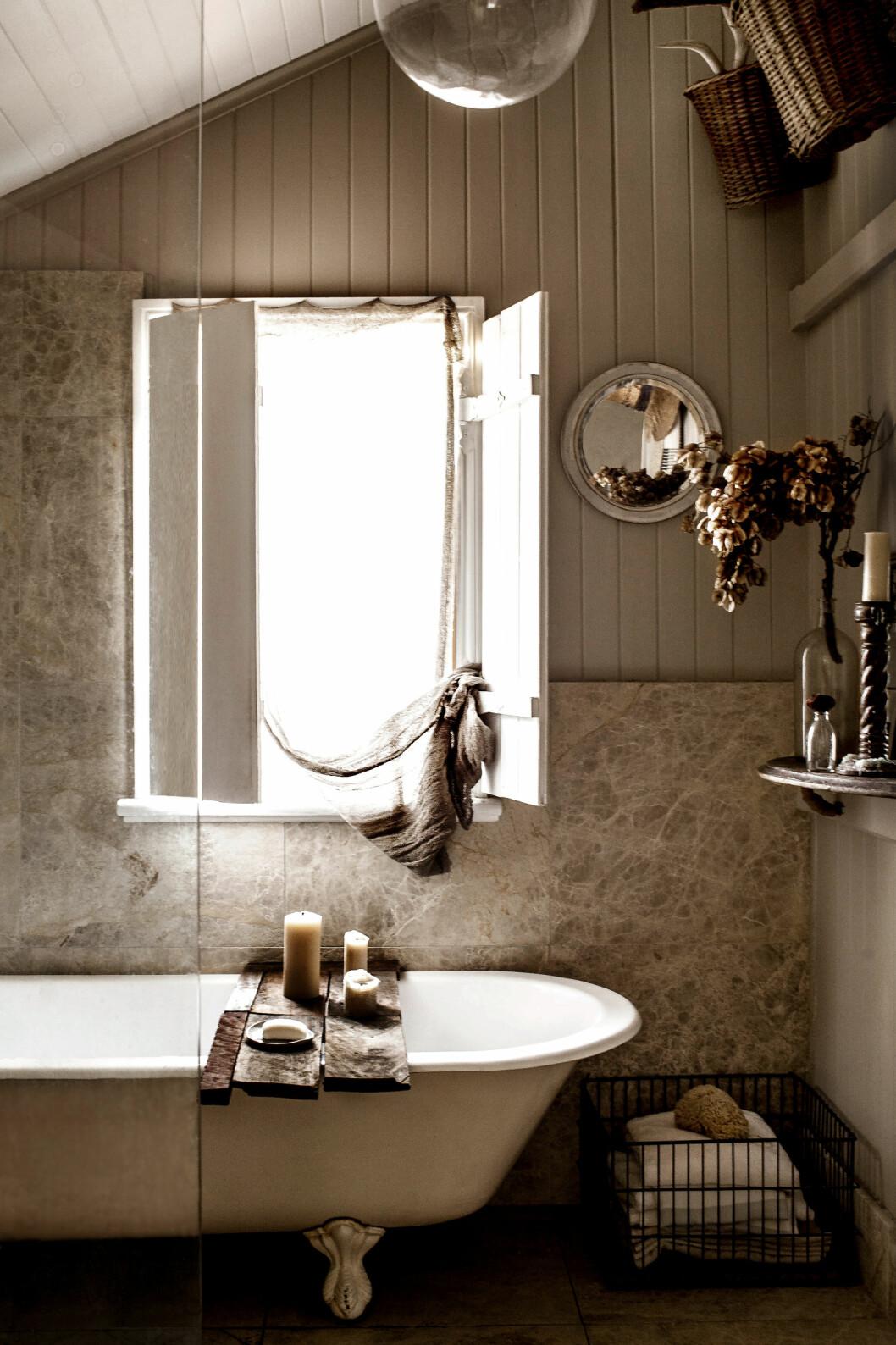 ENKELT: Enkel baderomsinnredning fremhever det vakre, gamle badekaret med ørneføtter. Et gammelt linstykke foran vinduet og mange stearinlys understreker den jordnære, harmoniske stemningen. Foto: Kara Rosenlund