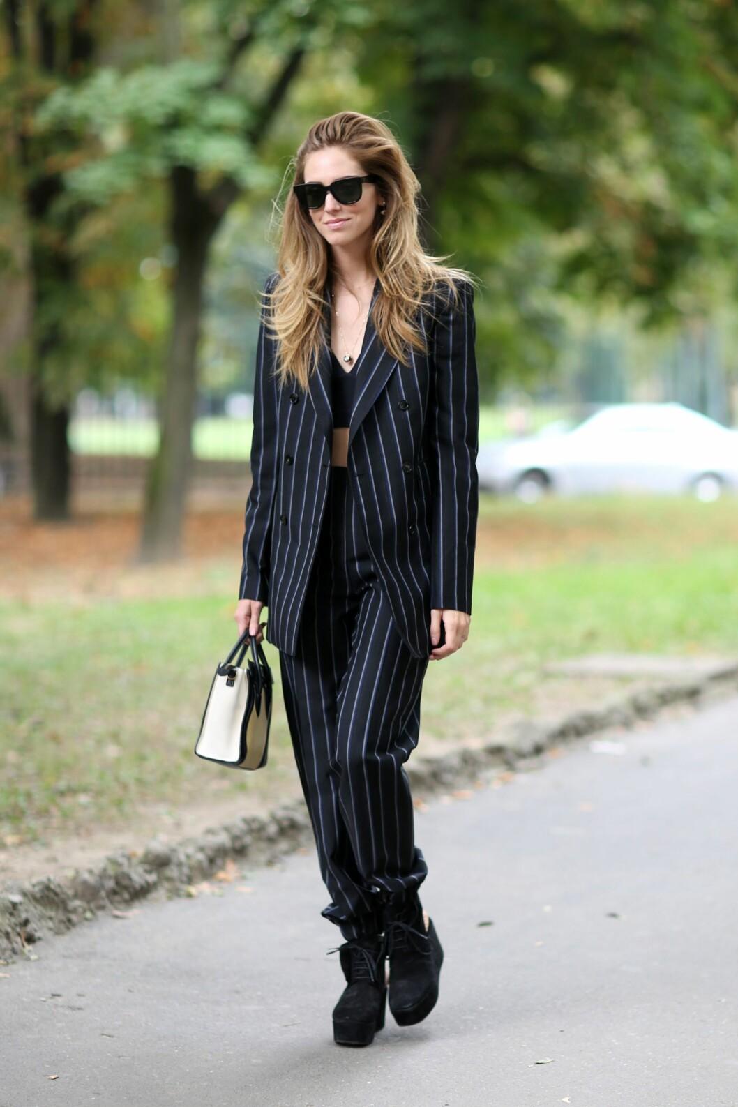 En fashionista styler sin pinstriped dress med helsvart tilbehør under moteuken i Milano.  Foto: All Over
