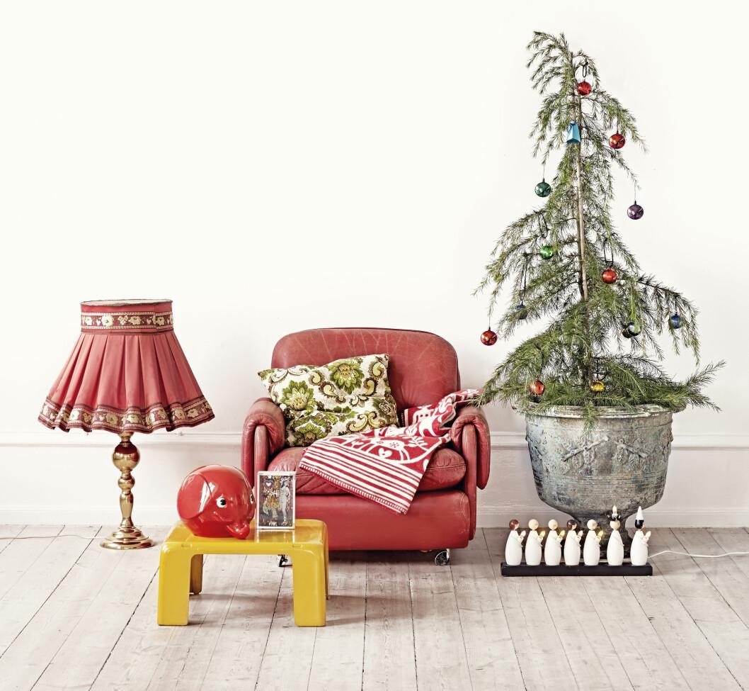 Skinnstolen er Ikea fra 70-tallet, kjøpt på bruktmarked. Messinglampen med stoffskjerm er kjøpt på loppis. Klippanpledd i stolen (kr 1200, klippanyllefabrik.se). Puten er vintage fra loppis. Stor, grønn krukke kan kjøpes via moinredning.com (kr 2800). Luciatoget er en klassiker fra 70-tallet, og kan kjøpes blant annet via elon.se (ca kr 700). Julekuler fra loppis. Gult bord i plast er italiensk og kjøpe på fildefer.dk for kr 3000 (det finnes tre deler til det). Den røde, klassiske sparegrisen er fra nyborgjagare.se (ca kr 500 for den største). Foto: Sara Svenningrud