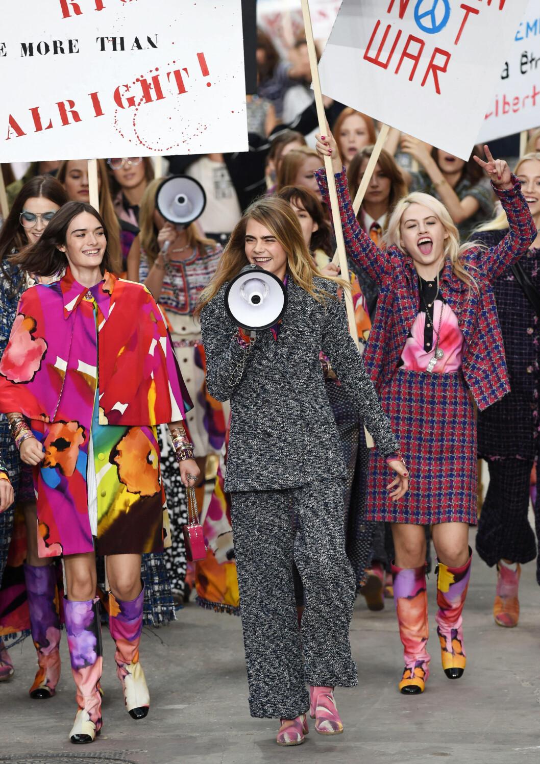 EN AV CHANELS MUSER: Supermodell Cara Delevingne, her med megafon på liksom-demonstrasjon på catwalken for Chanel, velger bort Victoria's Secret, siden det kærsjer med det franske motehuset. Foto: REX/David Fisher/All Over Press