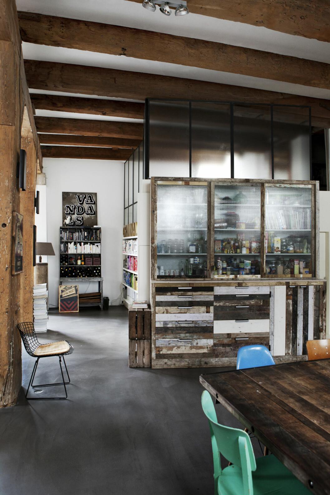 GJENNOMSIKTIG: Bak gjennomsiktig ruter ser man at dette er kjøkkenet, men stuen følger like etter. Legg merke til hvordan vinflasker er plassert i bokhyllen innerst i bildet! Foto: Pernille Kaalund/House of Pictures