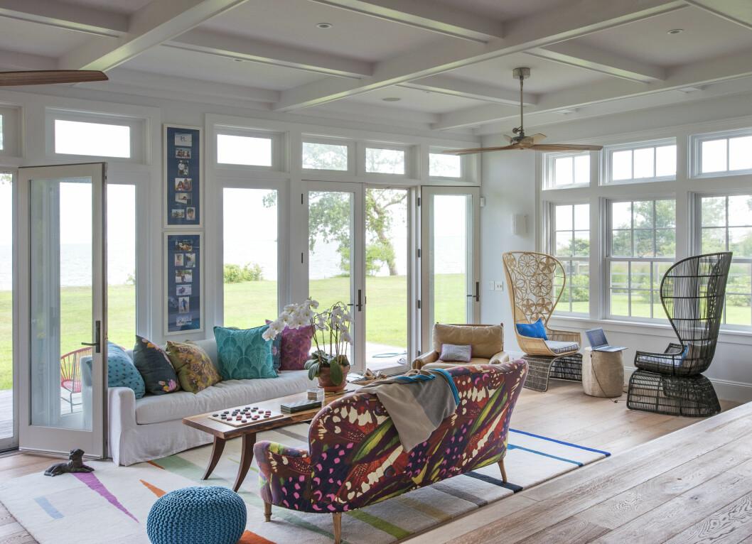 VAKKERT: De store vinduene bringer naturen helt inn i stuen, og blåtonene i interiøret reflekterer sjøen utenfor. Foto: Matthew Williams