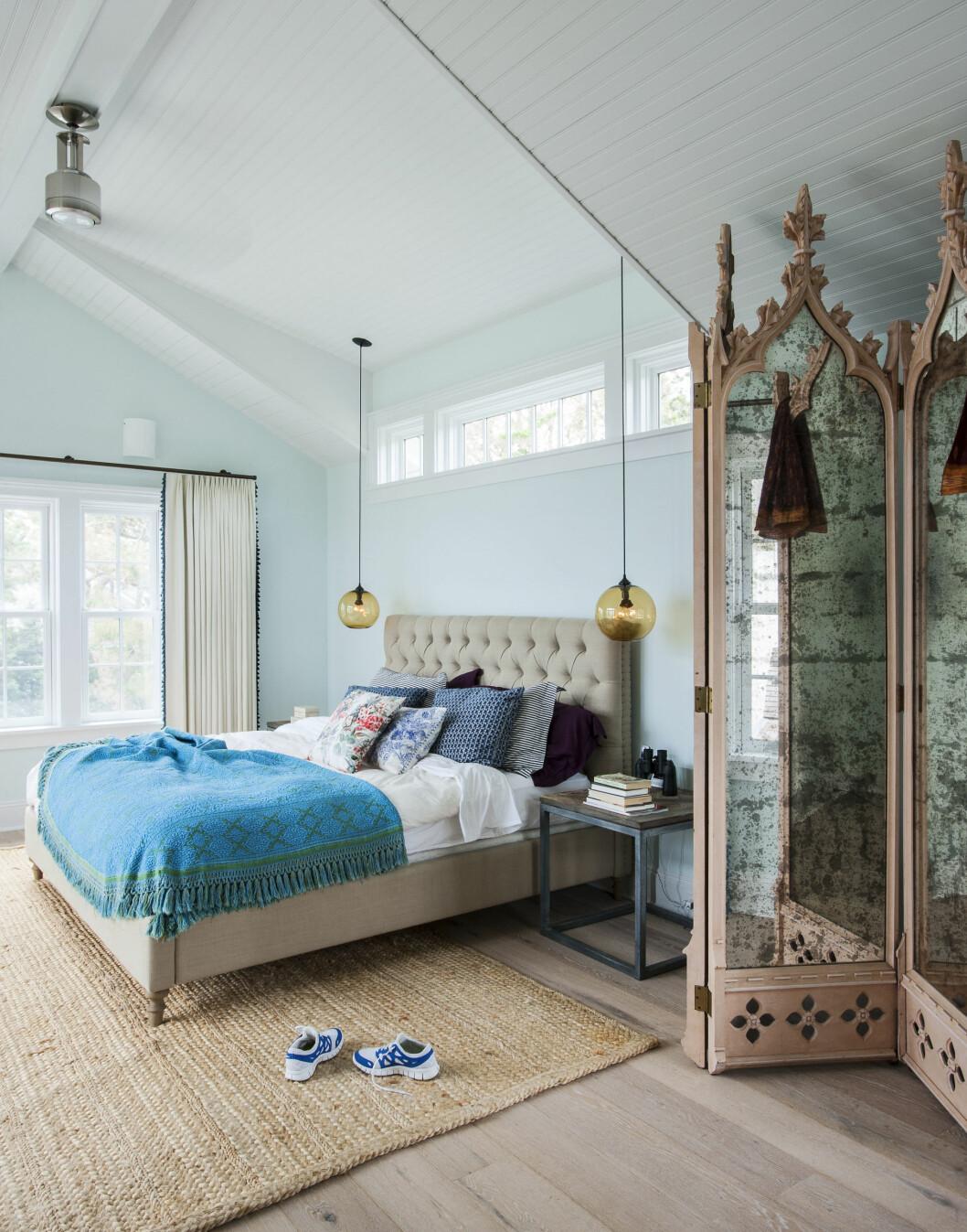 SOVEROMMET: Grønt og blått i alle tenkelige nyanser fungerer alltid sammen. Prøv med sengetøy og puter! De to lampene ved sengen heter «Binare Pendant Light» og er fra Jeremy Pyles. Det ornamenterte speilet til høyre er arvegods. Foto: Matthew Williams