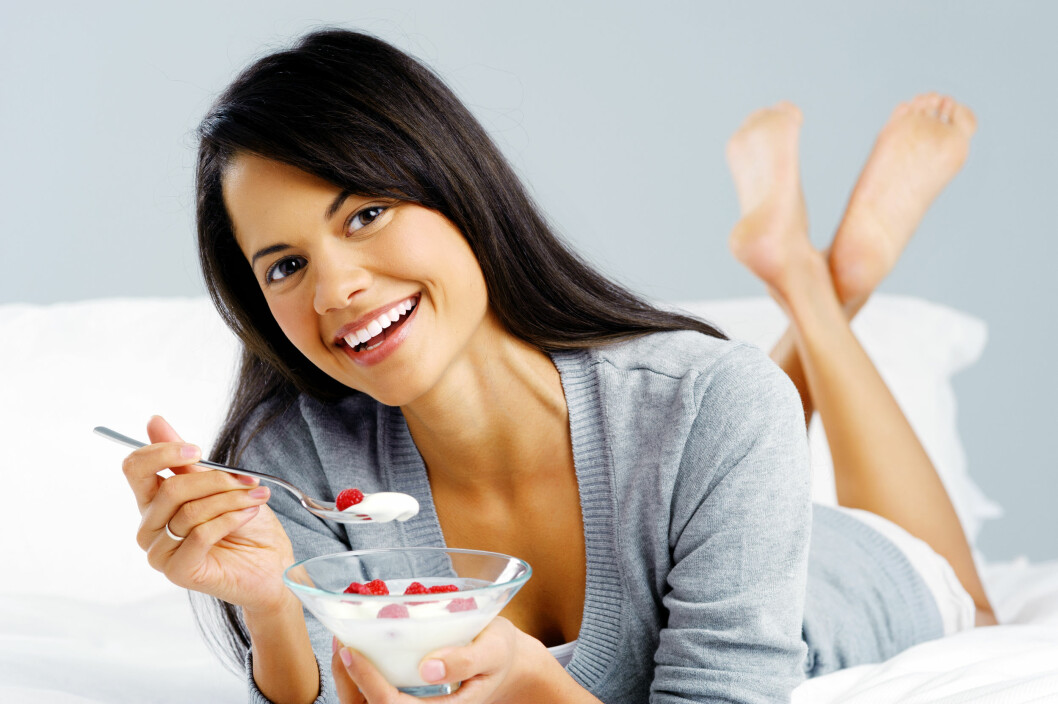 Portrait of a happy smiling latino hispanic woman eating a healthy breakfast of fruit and yoghurt in bed.  Foto: Warren Goldswain - Fotolia