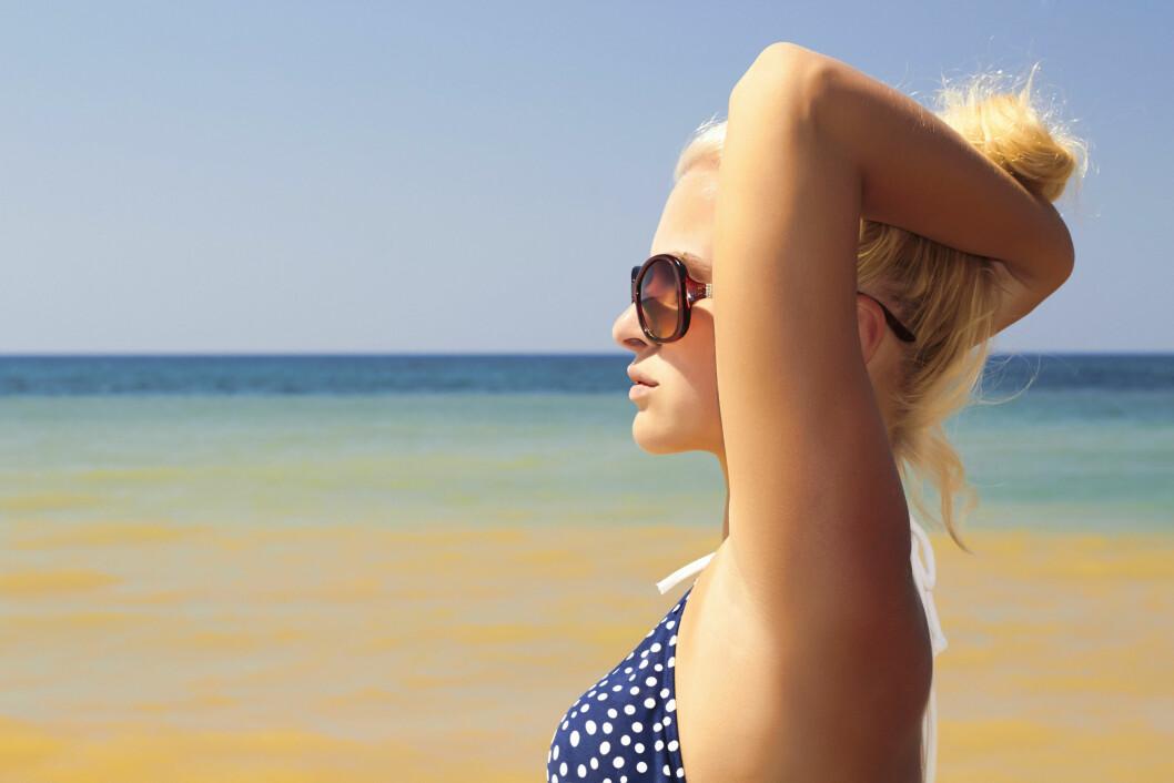 <strong>HØY TOPP:</strong> Fest hårtoppen høyt på hodet, gjerne enda høyere enn dette, og la håret tørke fullstendig mens du nyter en god bok på stranda.  Foto: eugenepartyzan - Fotolia