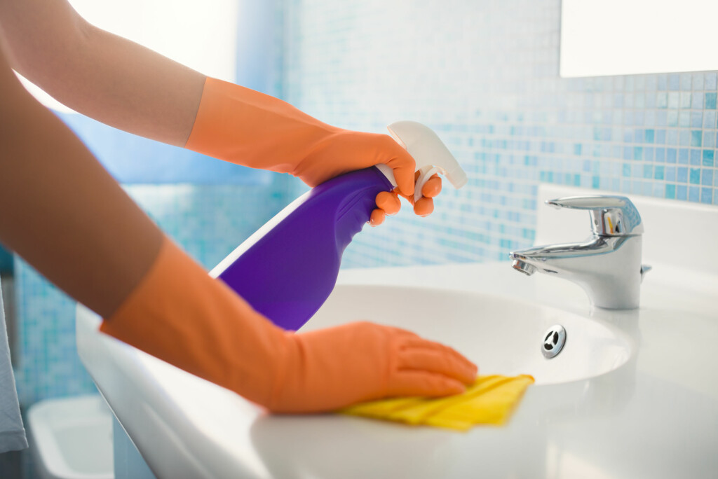 woman doing chores in bathroom at home, cleaning sink and faucet with spray detergent. Cropped view Foto: diego cervo - Fotolia