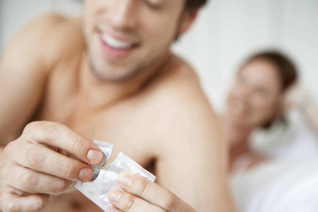 MODEL RELEASED Couple in bed, man opening condom,  of condom Foto: All Over Press