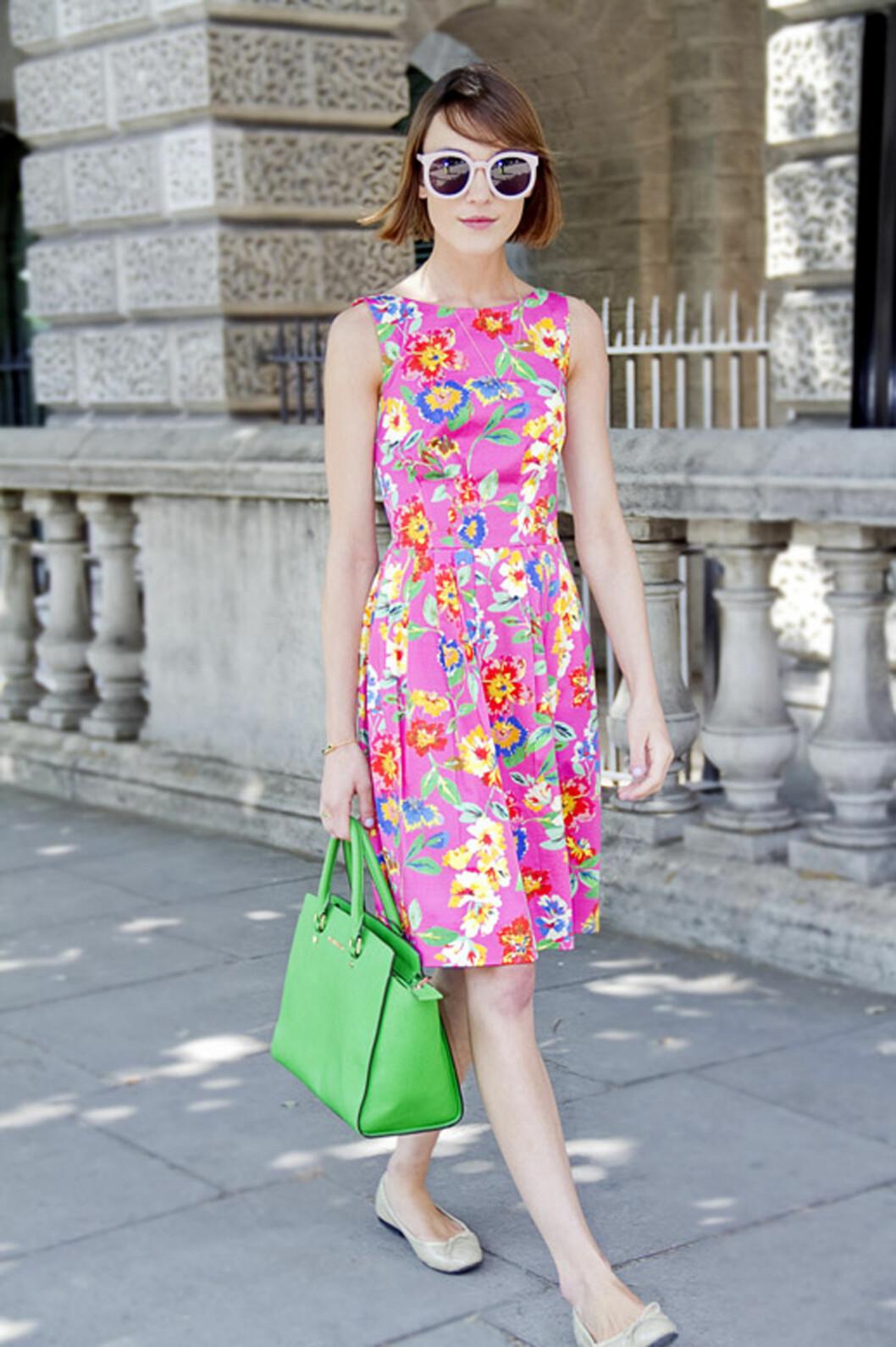 Stilikon Ella Catliff i blomstret kjole fra Kate Spade, solbriller fra Karen Walker og en knall grønn veske fra Michael Kors.  Foto: REX/Holly McGlynn/All Over Press