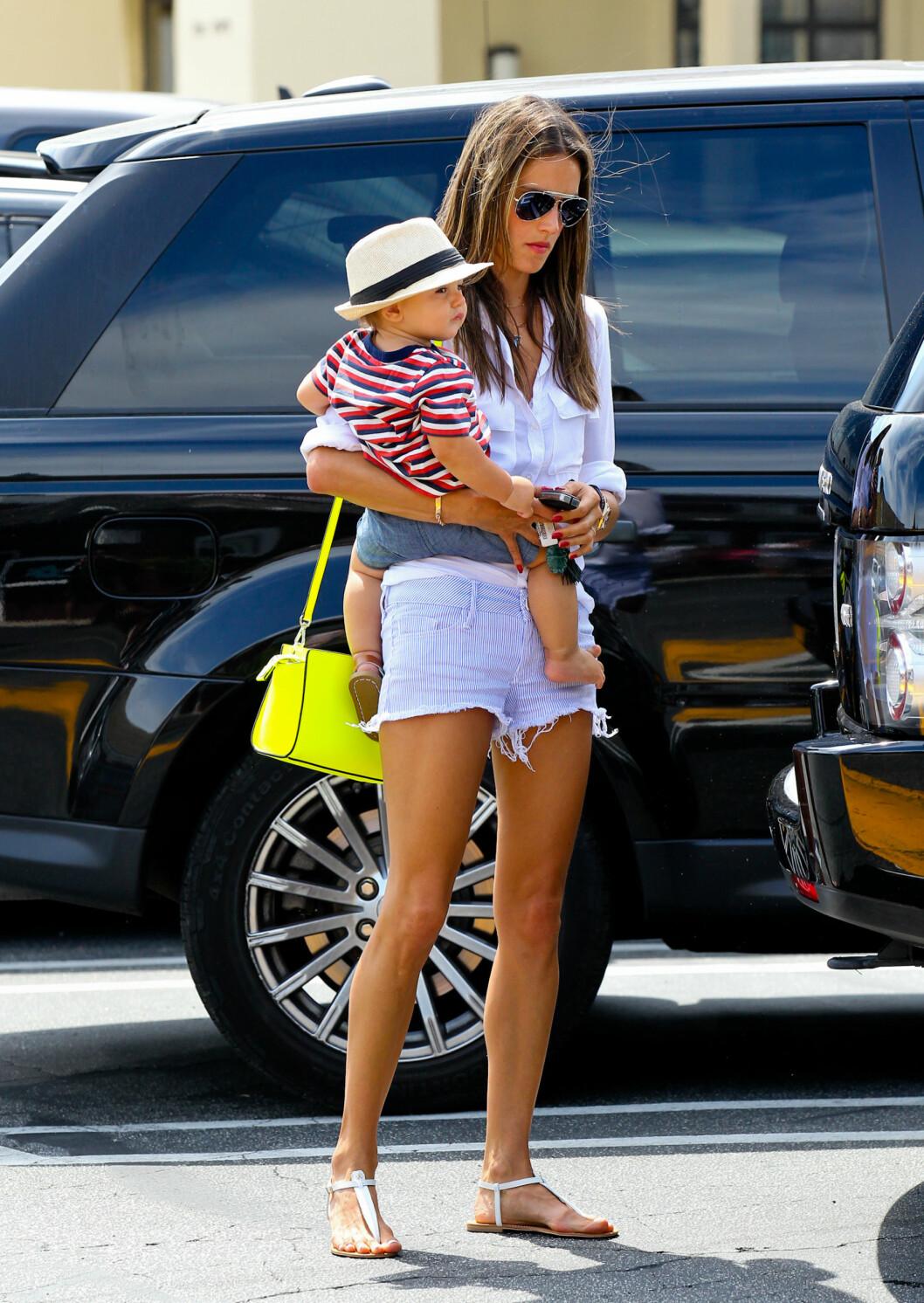 Supermodell Alessandra Ambrosio i stripete shorts, avslappet hvit skjorte og en knall gul veske fra Michael Kors. Foto: action press/All Over Press