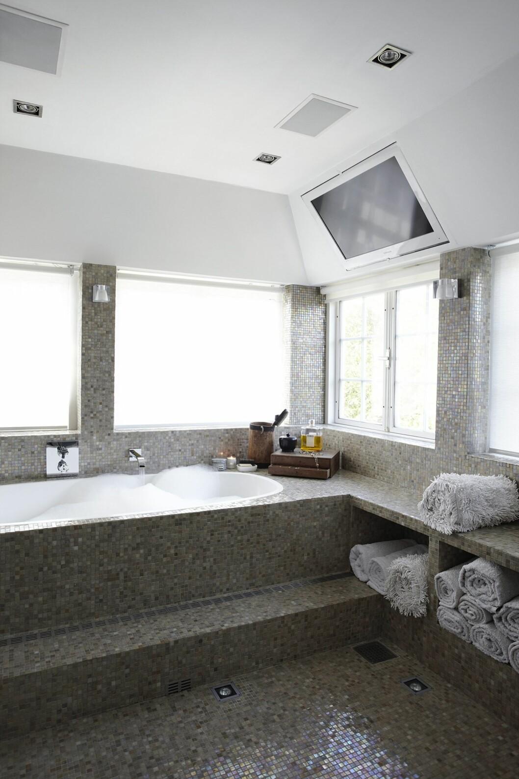 TV PÅ BADET: Det lekre baderommet er holdt i glassmosaikk med sandfarget perlemorseffekt, og det innebygde badekaret gir sammen med resten av innredningen en utsøkt spa-følelse. Sjekk også tv-en som er innebygd i taket. Foto: Kira Brandt Rasmussen