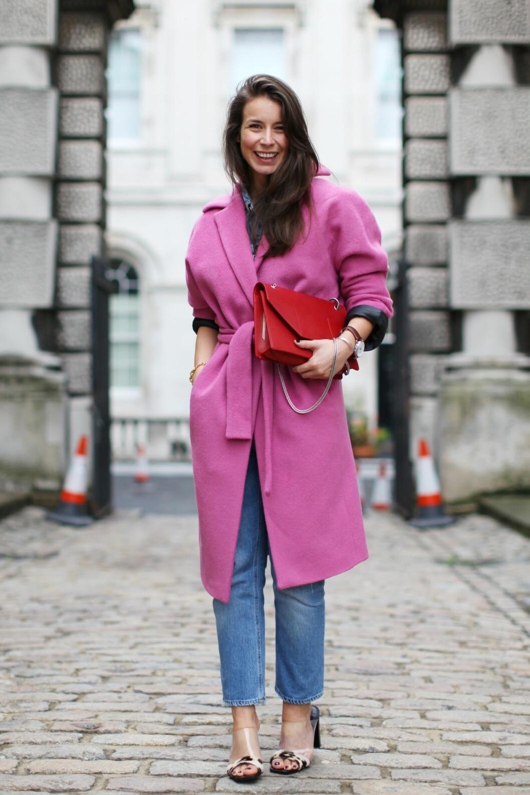 Den norske motebloggeren Irina Lakicevic stråler i rosa kåpe fra By Malene Birger og rød veske. Foto: All Over Press
