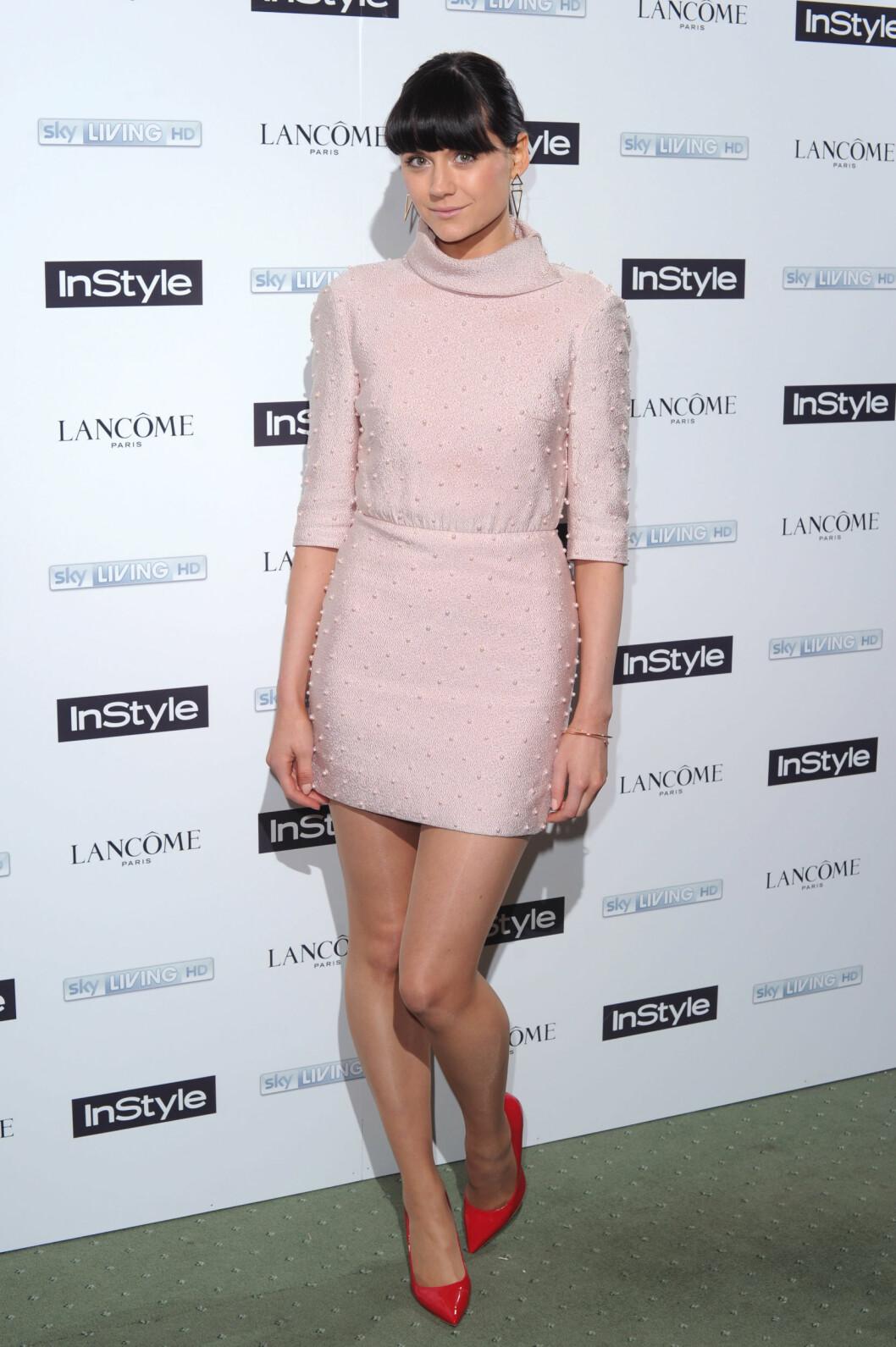 Lilah Parsons gjør den pastellfargede kjolen mer sexy med et par spisse, røde pumps. Foto: All Over Press