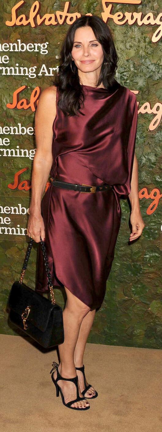 I BURGUNDERFARGET KJOLE MED KLEDELIG KNELANG LENGDE: Skuespiller Courteney Cox i nydelig drapert kjole med belte i livet.  Foto: REX/Stewart Cook/All Over Press