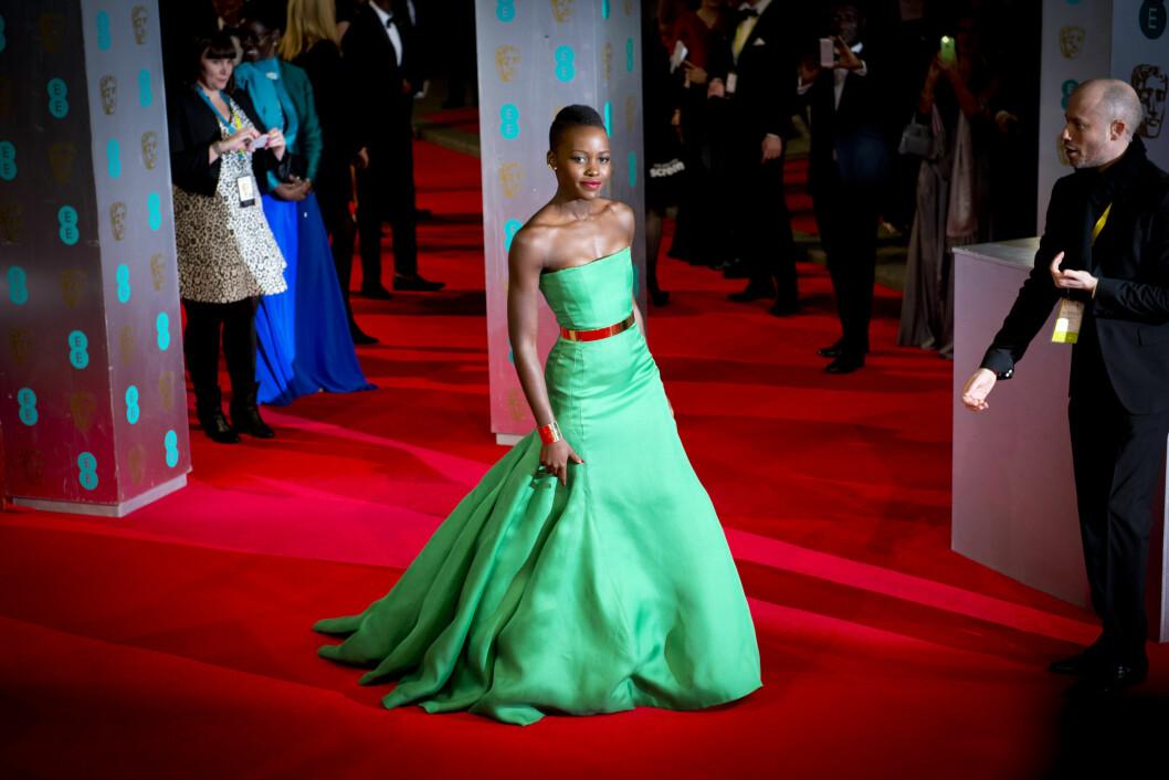 KNALLFARGER: Lupita Nyong'o stråler i sterke farger og enkle snitt på den røde løperen.  Foto: Empics Entertainment/All Over Press