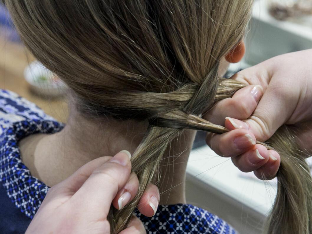 Samle alt håret på motsatt side av skillen. Del så håret i to like store deler. Ta litt hår fra yttersiden av den ene hårdelen, legg den over seksjonen du har tatt håret fra, og plasser den sammen med den andre hårdelen. Foto: Per Ervland