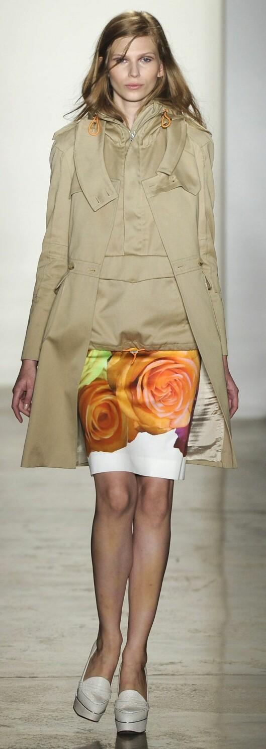 OVERDIMENSJONERT: Silkeksjørt med blomsterprint til khaki-farget anorakk/trenchcoat på catwalken til Peter Som.  Foto: All Over PressAll Over Press
