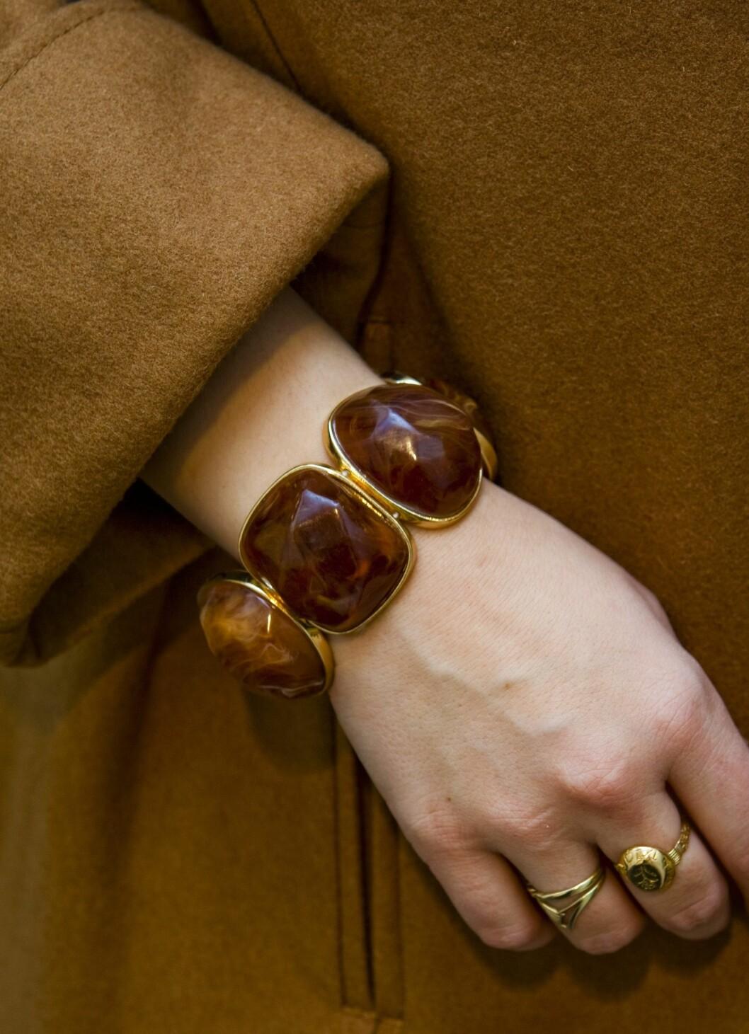 H&M har også masse rimelig tilbehør som passer til de respektive stilene for hver sesong. Et stort armbånd med plastikkstener i matchende brunt står fint både til kjolen og kåpen.