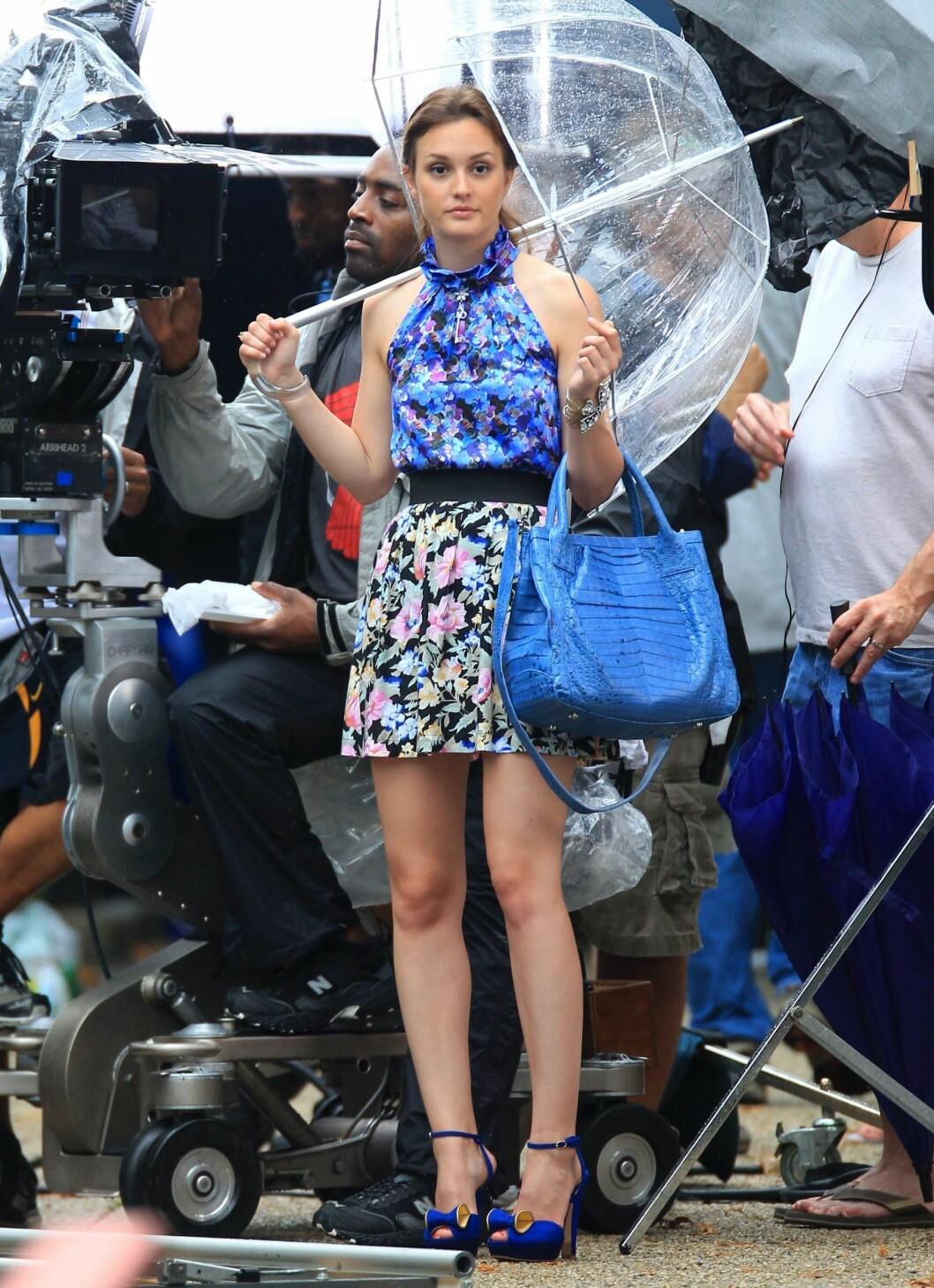 Blake Lively er kanskje lei av å vente på at værgudene skal samarbeide, men stråle gjør hun i blåmønstret topp, blomstrete miniskjørt og slående kongeblå accessoarer. Legg merke til de sexy skoene - ikke akkurat regntøy. Foto: All Over Press