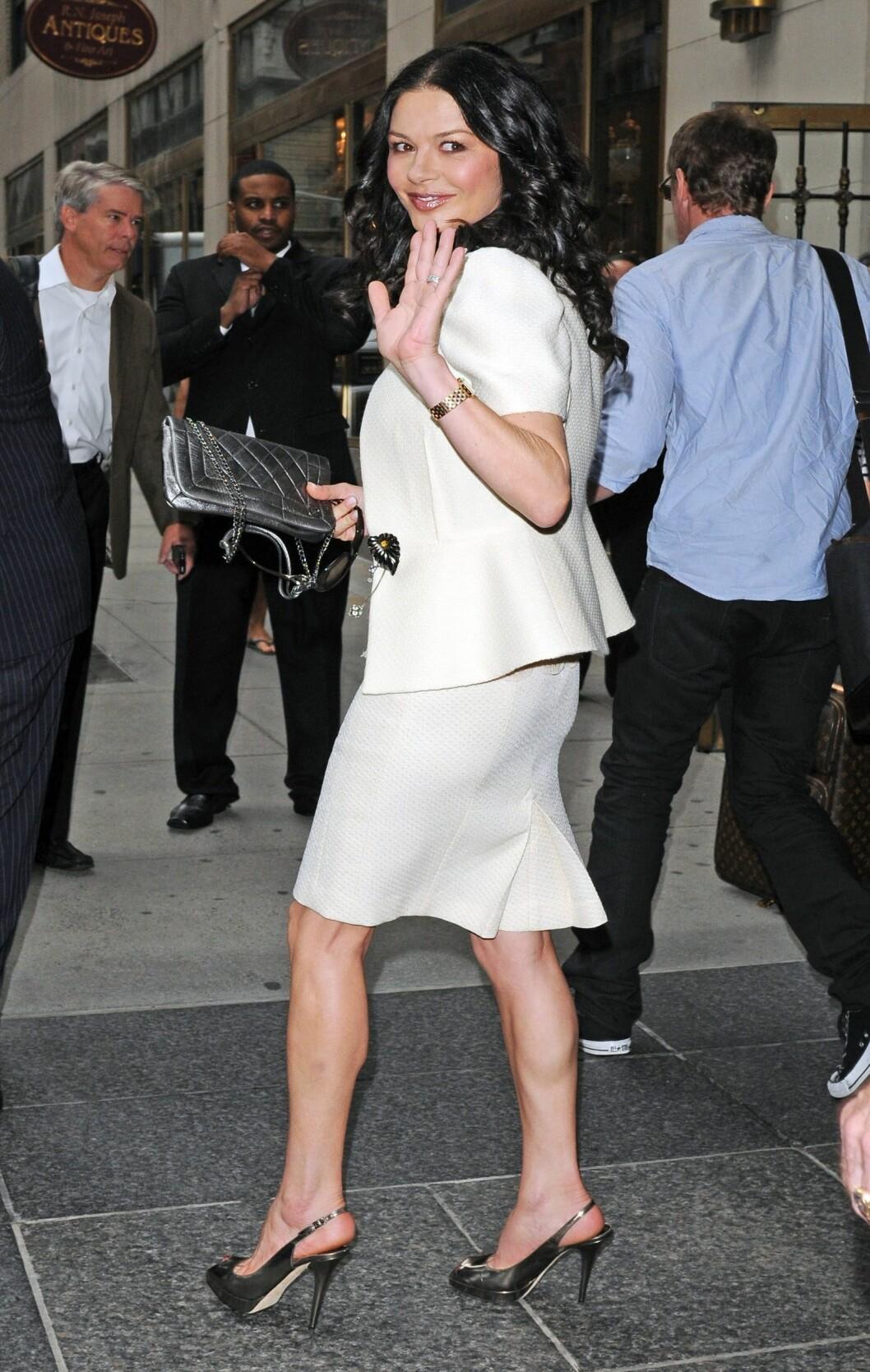 Catherine Zeta Jones i kremhvit drakt høye slingbacks i sølv og matchende clutchveske - også fra i fjor. Foto: All Over Press