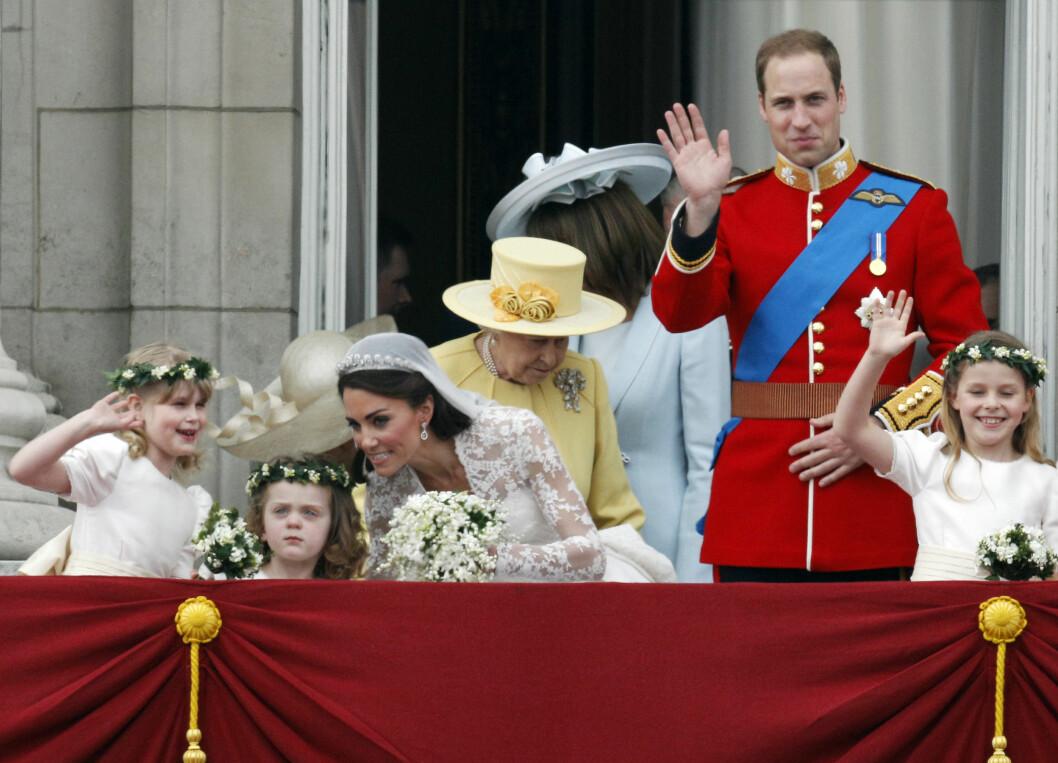 FIKK TRØST AV KATE: Da bruden la merke til at lille Grace fikk nok av alt oppstyret bøyde hun seg ned for å gi 3-åringen trøst på balkongen på Buckingham Palace. Til høyre er brudepike Lady Louise Windsor, i gult ser vi brudgommens farmor dronning Elizabeth, brudens mor Carole Middleton (i blått), prins William og brudepike Margarita Armstrong-Jones. Foto:  Foto: NTB Scanpix